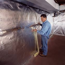 Installation of a radiant heat and vapor barrier on a basement wall in Ladner