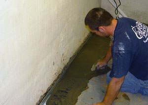 Restoring a concrete slab floor with fresh concrete after jackhammering it and installing a drain system in Deep Cove.